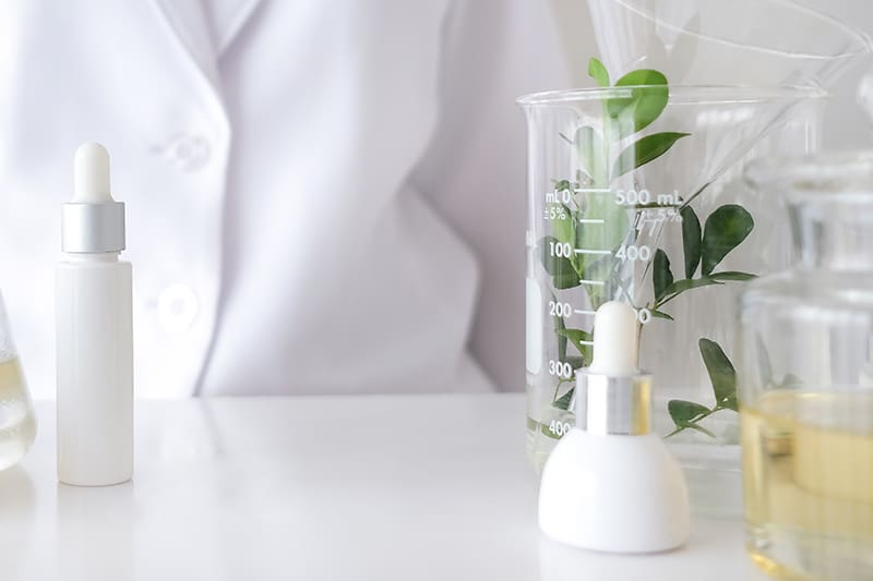 beaker and bottles with hair product formulations